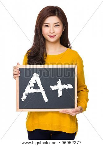 Woman with chalkboard showing A plus mark