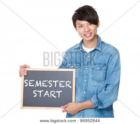 Man hold with blackboard showing phrase of semester start