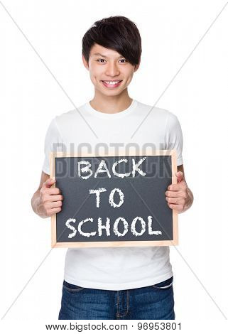 Young man hold with chalkboard showing phrases of back to school
