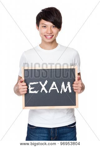 Young man hold with chalkboard showing a word exam