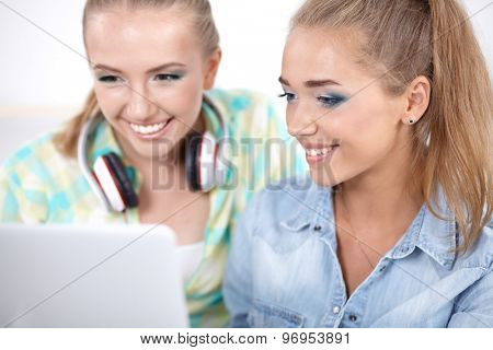 Two young women sitting with laptop , together