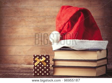 Santas Hat Over Books Near Gift Box