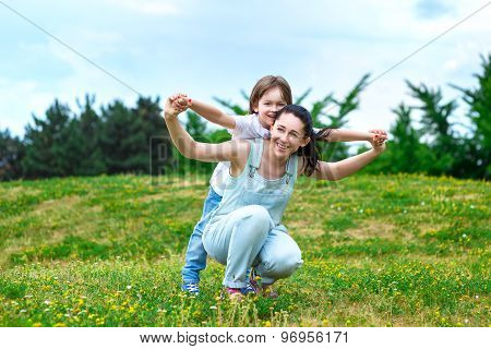Loving mother rolls on a back of small son in park. They playing fun game.