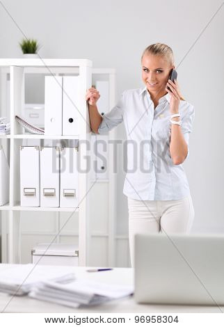 Young business woman standing in office talking on her mobile phone.