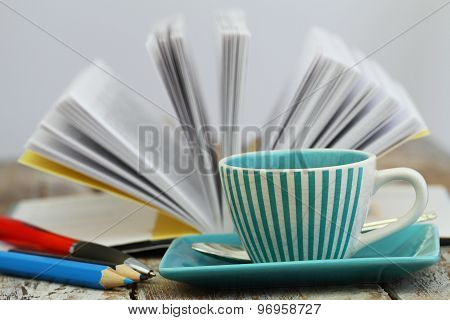 Cup of coffee with open book in the background