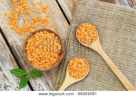 Uncooked red lentils on rustic wooden surface