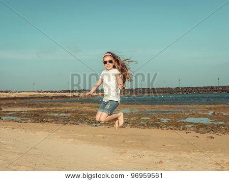 little girl jump on a sandy beach