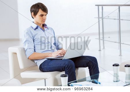 Young handsome businessman sitting and using laptop