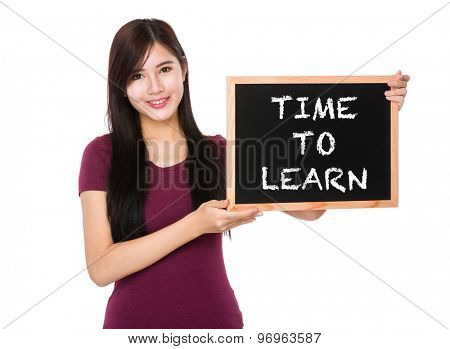 Asian woman hold with the blank chalkboard showing phrase time to learn