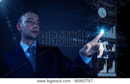 Young businessman pressing icon of media screen