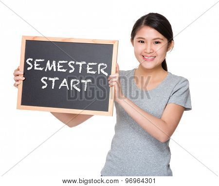 Young student hold with black board showing phrase semester start