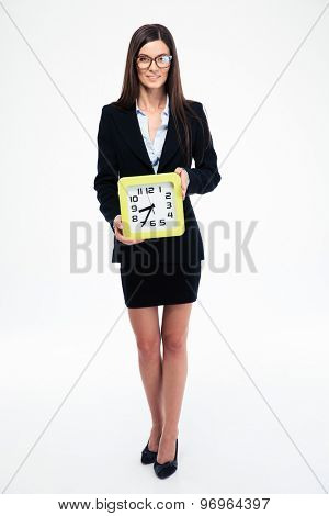Full length portrait of a businesswoman holding clock isolated on a white background. Looking at camera