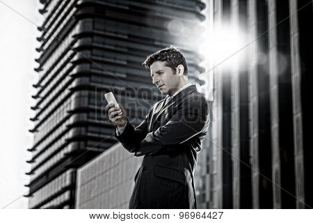 Attractive Businessman In Suit And Necktie Looking Text Message At Mobile Phone