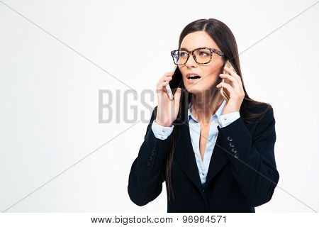 Businesswoman talking on two phones isolated on a white background