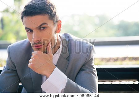 Portrait of a pensive businessman sitting on the bench outdoors