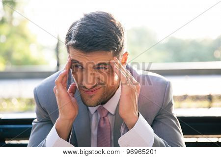 Portrait of a businessman sitting on the bench outdoors and having headache
