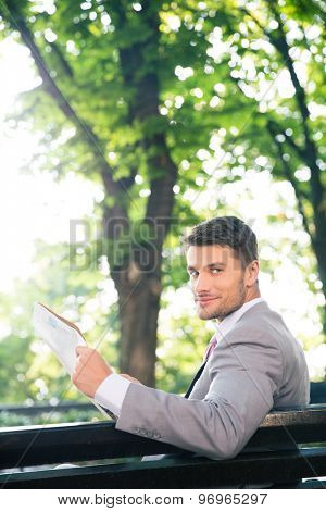 Smiling businessman sitting on the bench with newspaper and looking at camera outdoors
