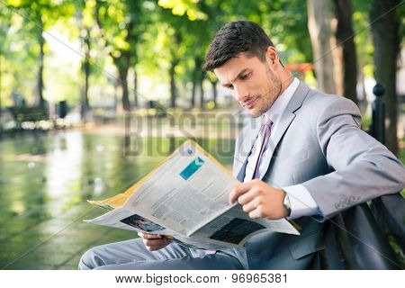 Portrait of a young businessman sitting on the bench and reading newspaper outdoors