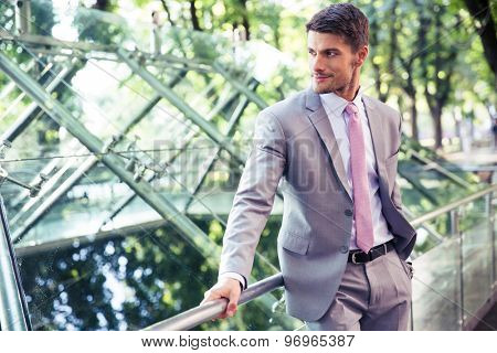 Portrait of a pensive businessman standing outdoors near glass building