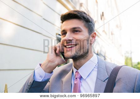 Portrait of a smiling businessman talking on the phone outdoors