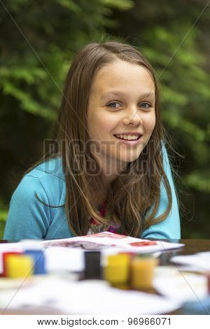 Portrait of little girl during painting paints.