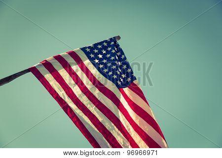 American flag over blue sky ( Filtered image processed vintage effect. )