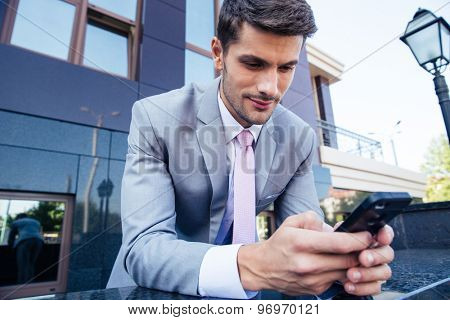 Handsome businessman using smartphone outdoors near office building