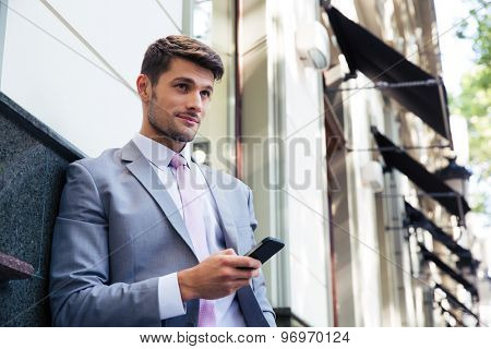 Portrait of a pensive businessman holding smartphone outdoors and looking away