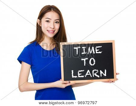 Student hold with wooden chalkboard showing phrase time to learn