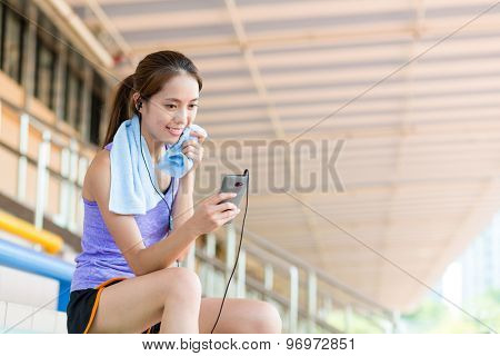 Asian girl take a break and listen to music and sitting on sport arena
