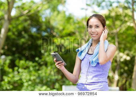 Sporty woman hold with cellphone and listen to music