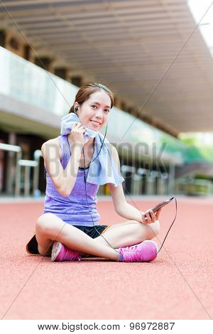 Young Woman listen to music and sitting on sport stadium