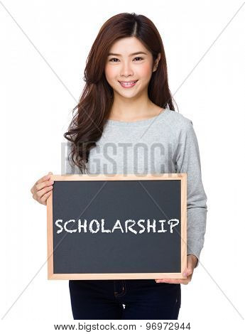 School girl hold with chalkboard and showing a word scholarship