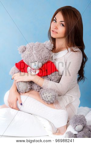 Beautiful Young Woman With Teddy Bear In A Bed