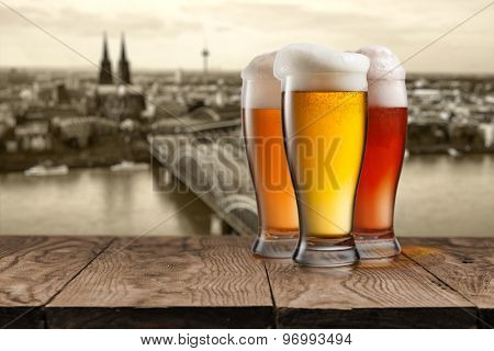Glass of beer on wooden table with view of Koln on background, Germany