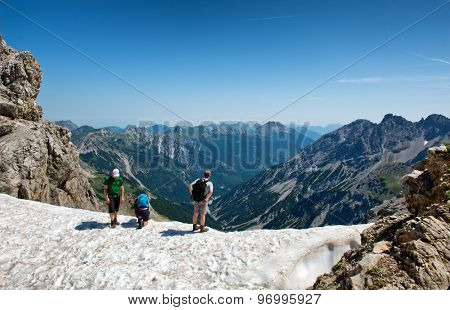 HOCHVOGEL, GERMANY - 05 JULY: Climbers on top of the Kalter Winkel upfold, looking over a rocky ledge at the mountain ranges and valley below, view from behind at Hochvogel, Germany on May 05, 2015