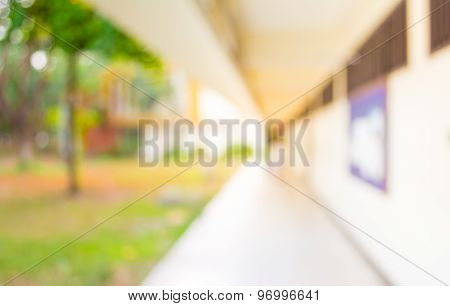 blur image of Long empty corridor with open space to the green garden with bokeh for background usag