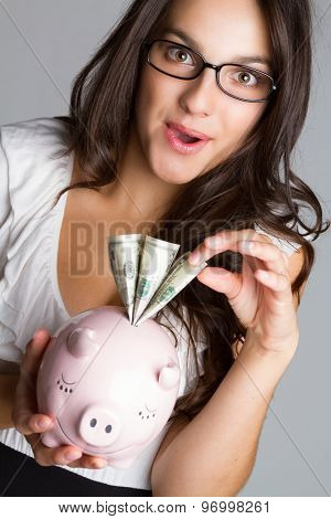 Business woman taking money from piggy bank