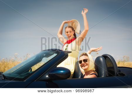 Women going in convertible car having fun on trip enjoying their freedom