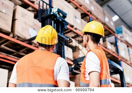 Worker team taking inventory in logistics warehouse
