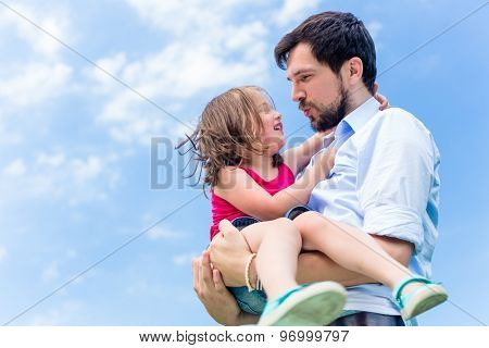 Father carrying daughter in his hands protecting her