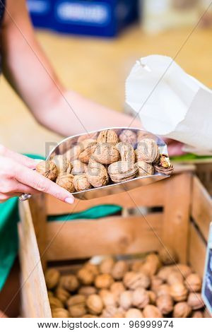 Female Supermarket clerk filling walnuts in bags at fresh department