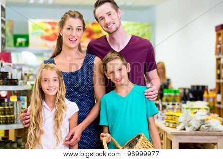 Parents and children selecting vegetables while grocery shopping in organic supermarket