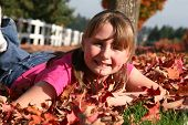 stock photo of school child  - teen in the leafs having fun with a smile - JPG