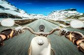 pic of slippery-roads  - Biker rides a motorcycle on a slippery road through a mountain pass in Norway - JPG