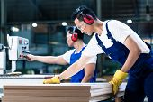 stock photo of sawing  - Two wood workers in carpentry cutting boards putting them in saw - JPG