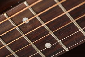 stock photo of string instrument  - Empty wooden rosewood fingerboard of classic acoustic guitar closeup - JPG