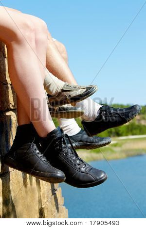 Image of three pairs of feet in boots on background of river, trees and sky