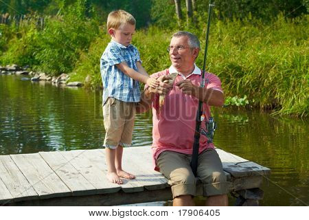 Photo of grandson looking at fish caught by his grandfather
