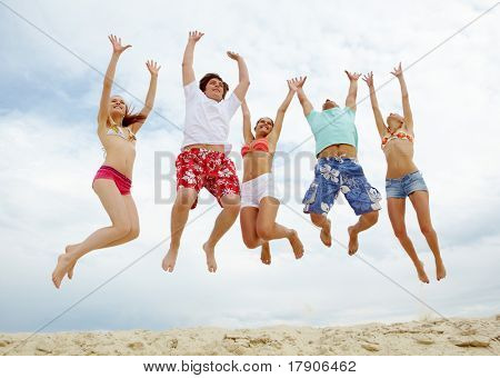 Photo of five friends in high jump over sandy beach